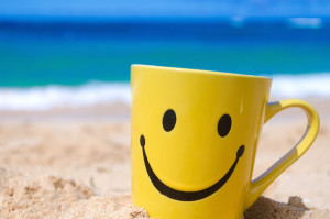 Happy face mug on the sandy beach
